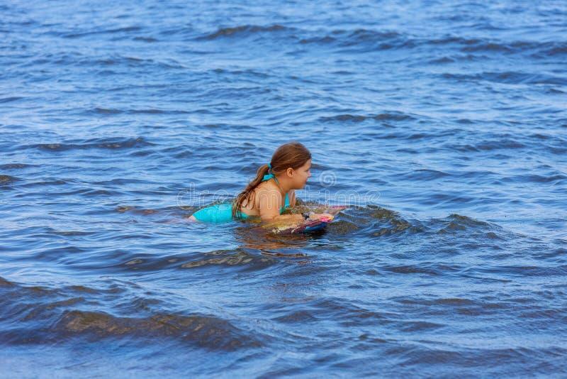 Paseo joven de la persona que practica surf del bebé feliz el vacaciones de verano de la familia de la tabla hawaiana imagenes de archivo