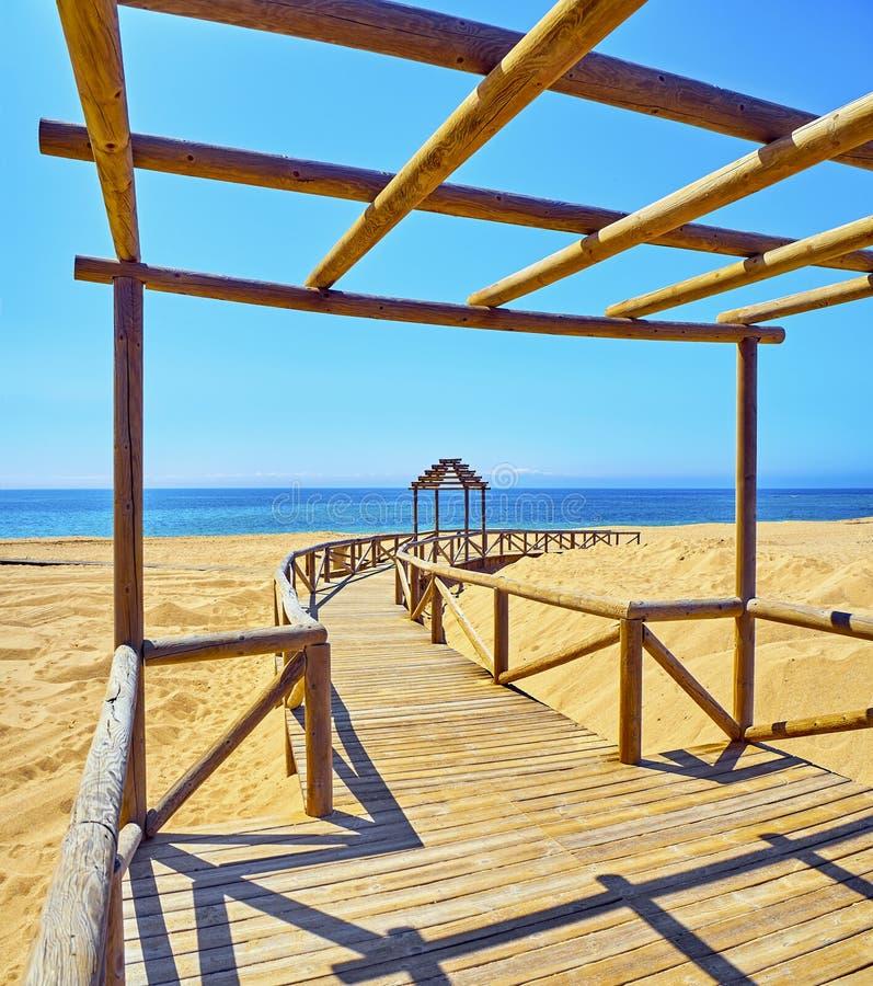 Paseo marítimo de madera que va a una playa amplia de las dunas de arena finas en un día soleado imagen de archivo libre de regalías