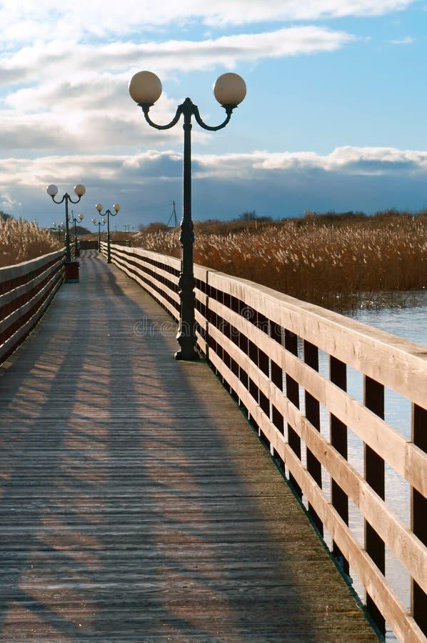 Paseo marítimo de madera a través de las cañas en la luz del sol, una 'promenade' de madera del tablón con los faroles fotos de archivo