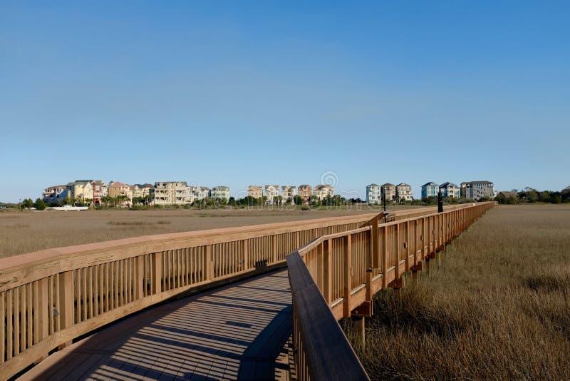 Paseo marítimo de madera y comunidad costera foto de archivo