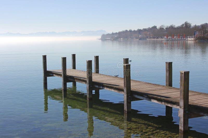 Paseo marítimo en el lago del starnberg, paisaje de la mañana con niebla y mounta fotografía de archivo