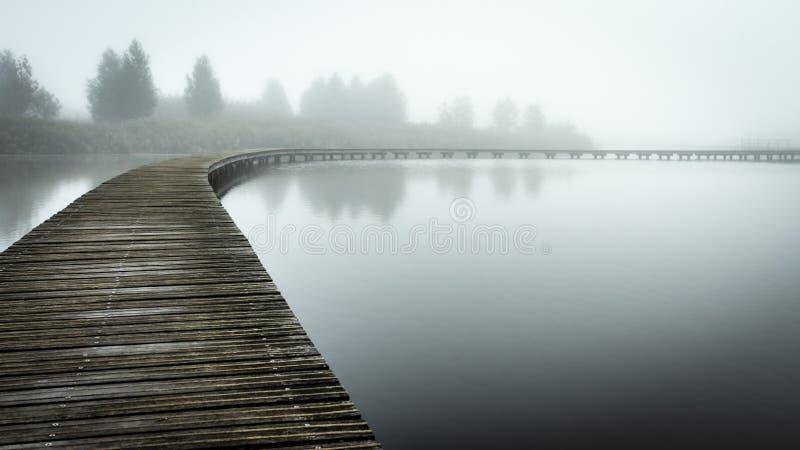 Paseo marítimo sobre el agua inmóvil en la niebla imagenes de archivo