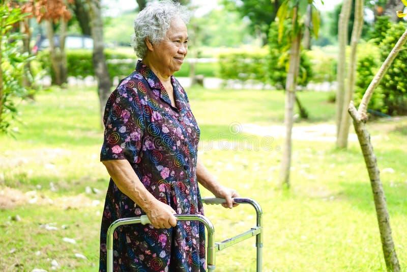 Paseo paciente asiático de la mujer mayor o mayor de la señora mayor con el caminante en parque: concepto médico fuerte sano fotografía de archivo