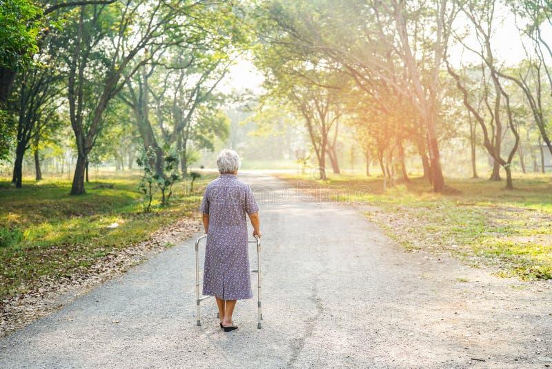 Paseo paciente asi?tico de la mujer mayor o mayor de la se?ora mayor con el caminante en parque fotografía de archivo libre de regalías