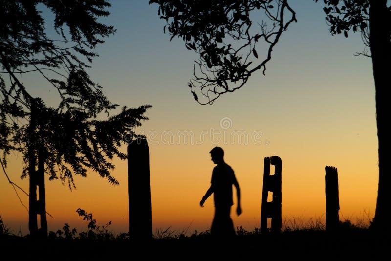 Paseo por la silueta del hombre de la puesta del sol imagenes de archivo