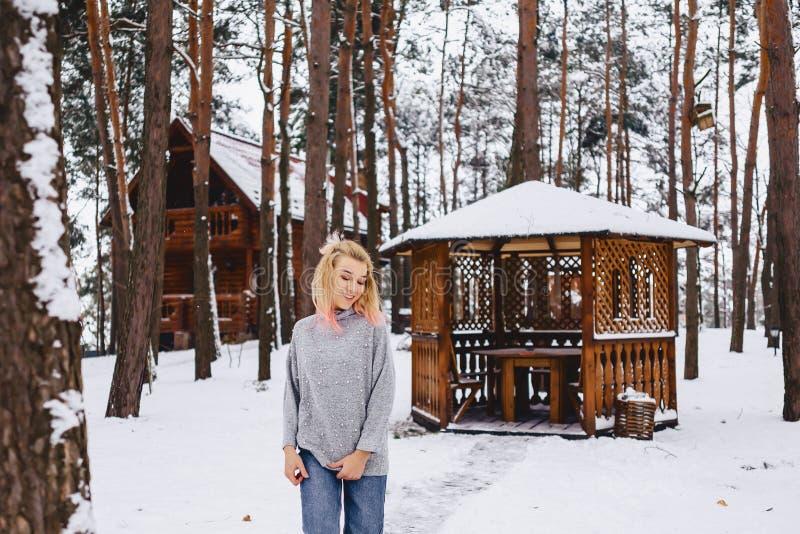 Paseo rubio de la muchacha cerca de un gazebo en el bosque del invierno imagen de archivo