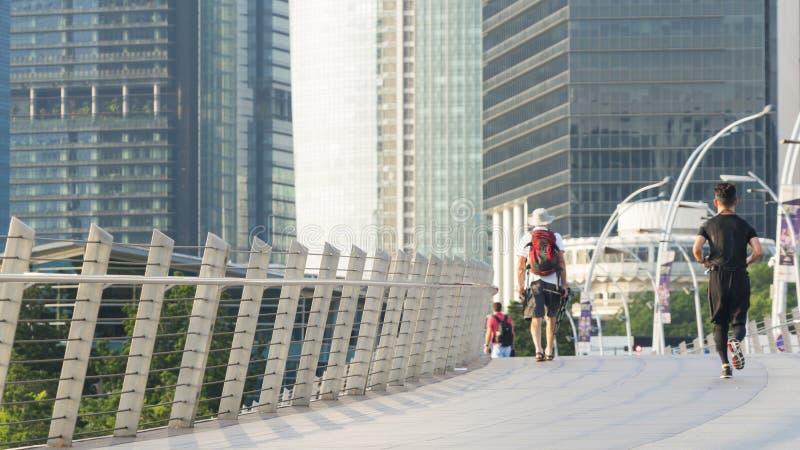 Paseo turístico en puente peatonal de la ciudad con el buil moderno exterior imagen de archivo