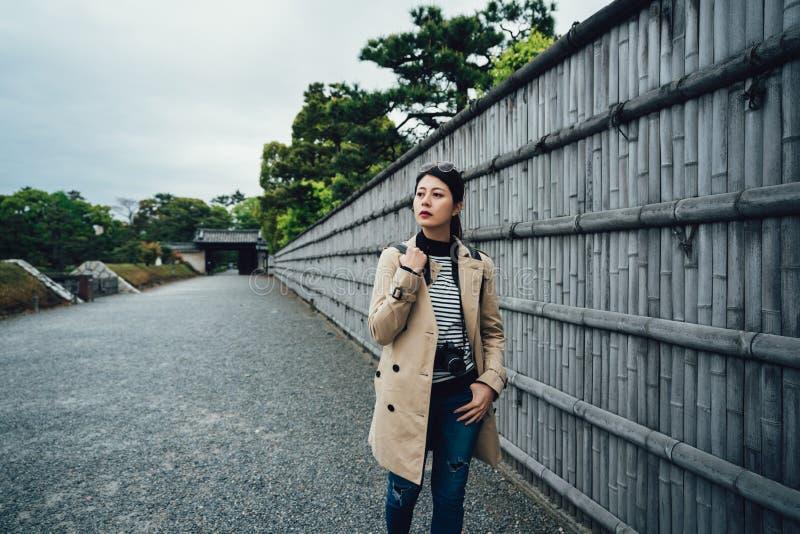 Paseo turístico a lo largo de la pared de bambú en el camino de piedra fotografía de archivo