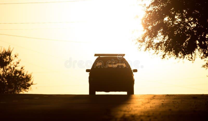 Paseos del coche en el camino en la puesta del sol fotos de archivo