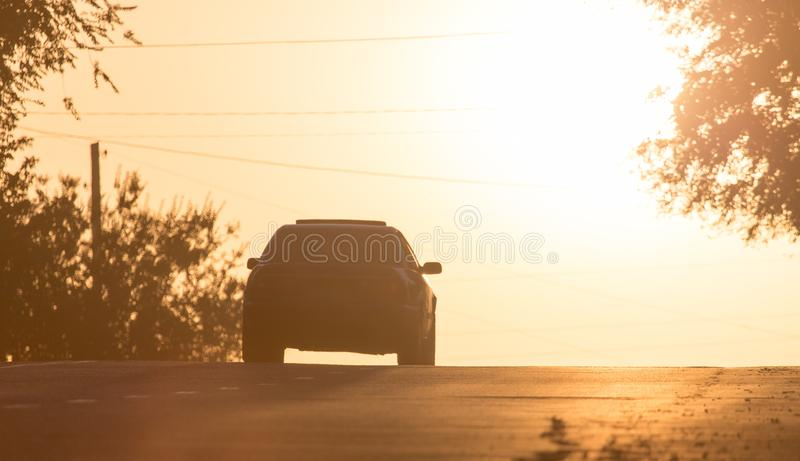Paseos del coche en el camino en la puesta del sol imagenes de archivo