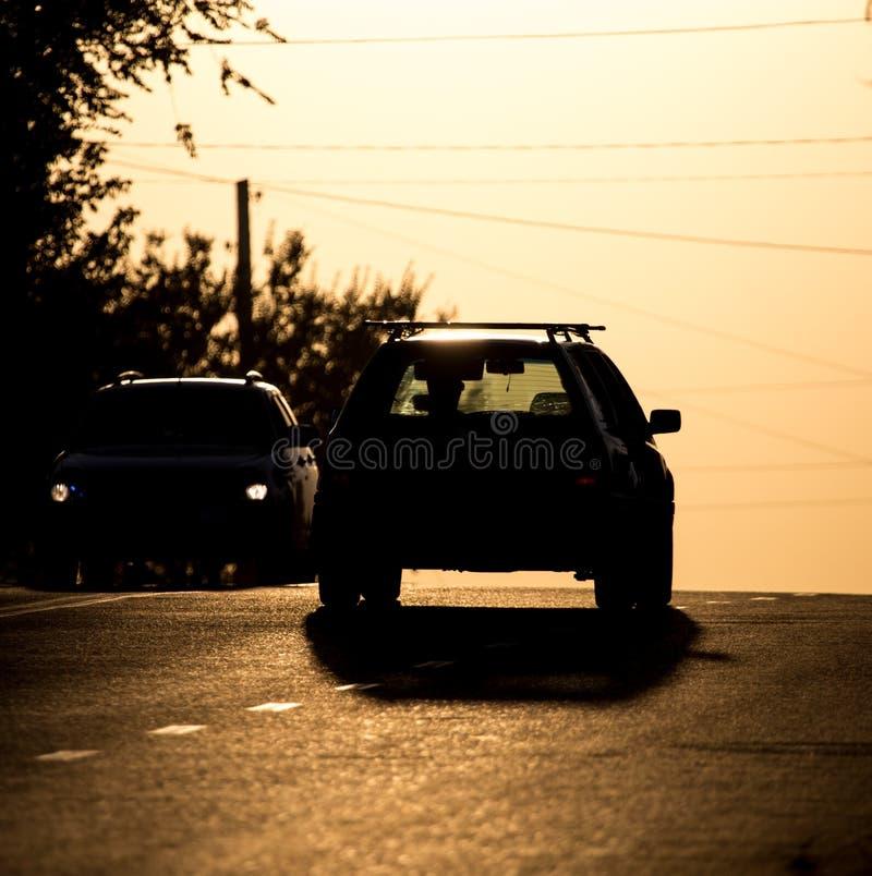 Paseos del coche en el camino en la puesta del sol fotografía de archivo libre de regalías