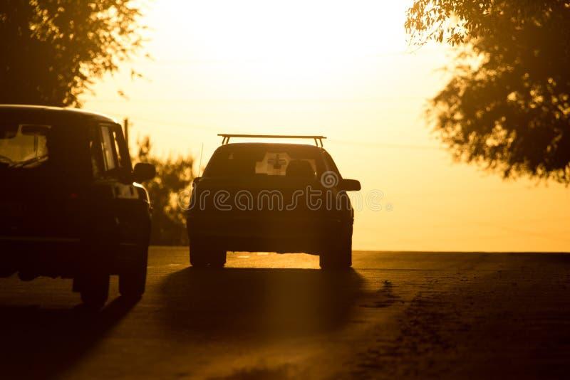 Paseos del coche en el camino en la puesta del sol foto de archivo