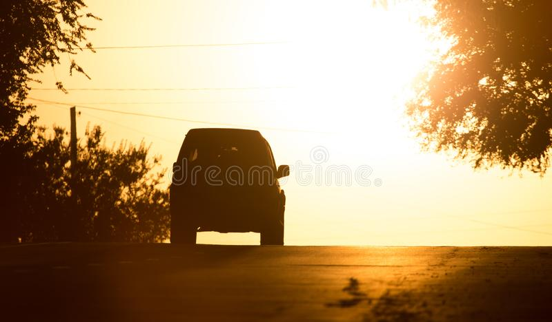 Paseos del coche en el camino en la puesta del sol imágenes de archivo libres de regalías