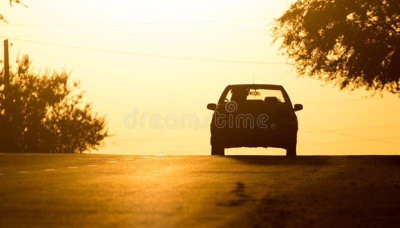 Paseos del coche en el camino en la puesta del sol foto de archivo libre de regalías