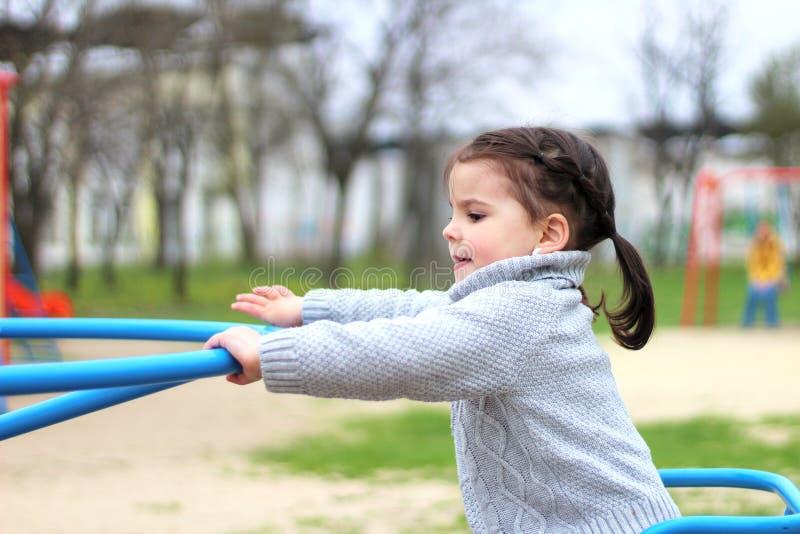 paseos del niño en el carrusel en el patio fotos de archivo libres de regalías