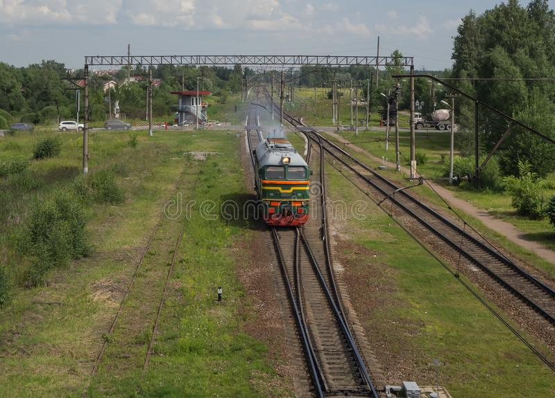Paseos del tren en los carriles en la estación Silueta del hombre de negocios Cowering foto de archivo