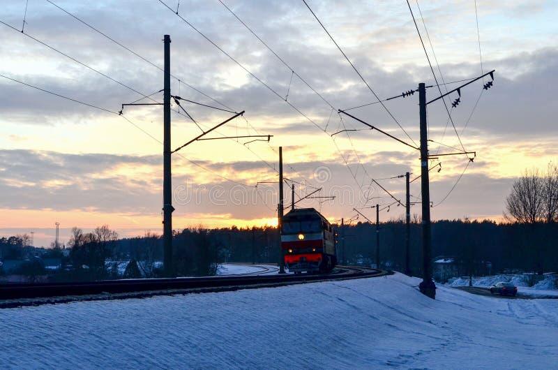 Paseos en tren en la puesta del sol, los rayos del tren de pasajeros del sol del sol en el invierno foto de archivo
