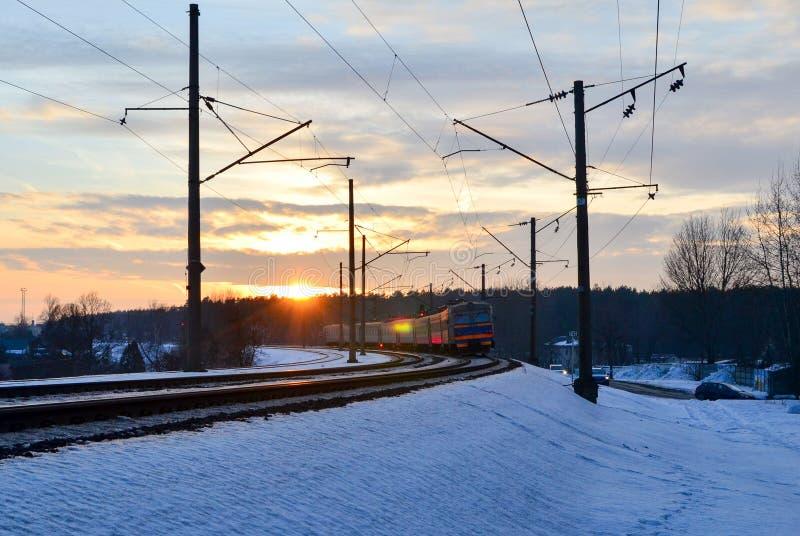 Paseos en tren en la puesta del sol, los rayos del tren de pasajeros del sol del sol imagen de archivo