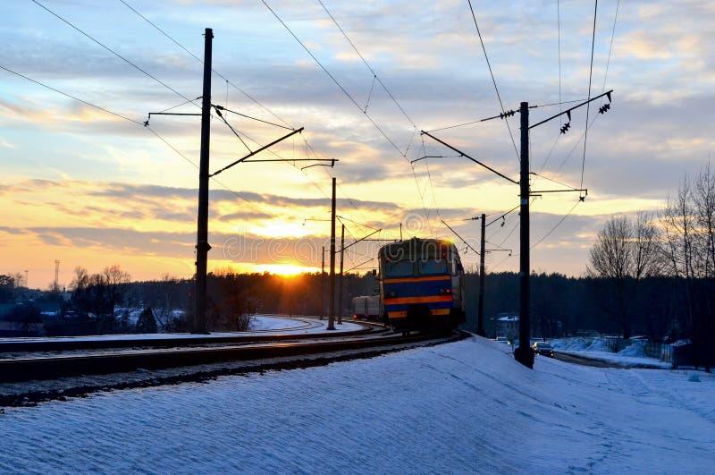 Paseos en tren en la puesta del sol, los rayos del tren de pasajeros del sol del sol imágenes de archivo libres de regalías