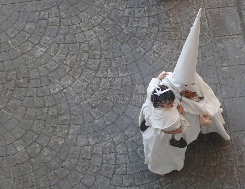Paseos penitentes en la calle con un bebé en la procesión de la semana santa fotos de archivo