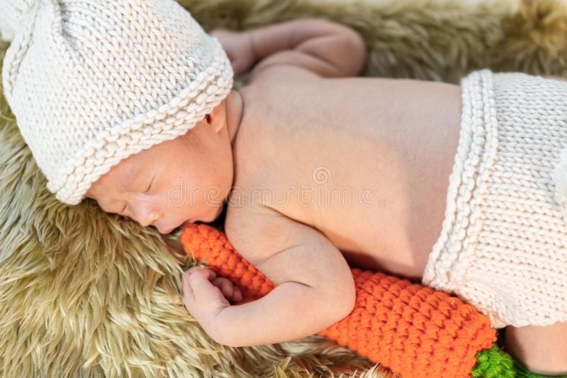 Pasgeboren baby in de slaap van het konijntjeskostuum op bontbed royalty-vrije stock foto's