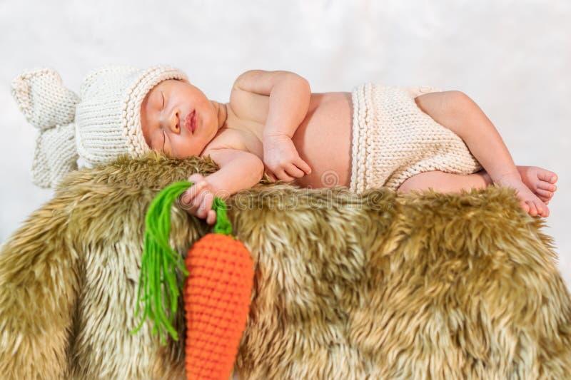 Pasgeboren baby in de slaap van het konijntjeskostuum op bontbed stock afbeeldingen