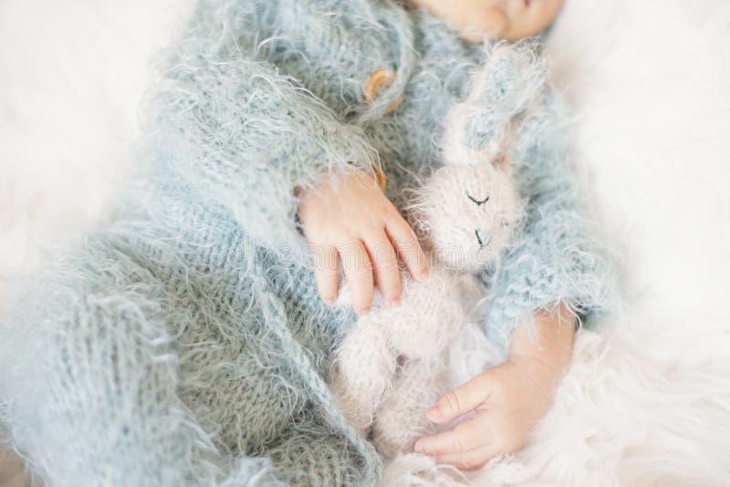 Pasgeboren baby Slaapende baby in bed, terwijl hij een Bunny Toy vasthoudt Baby met blauw-gebreide Romper royalty-vrije stock fotografie