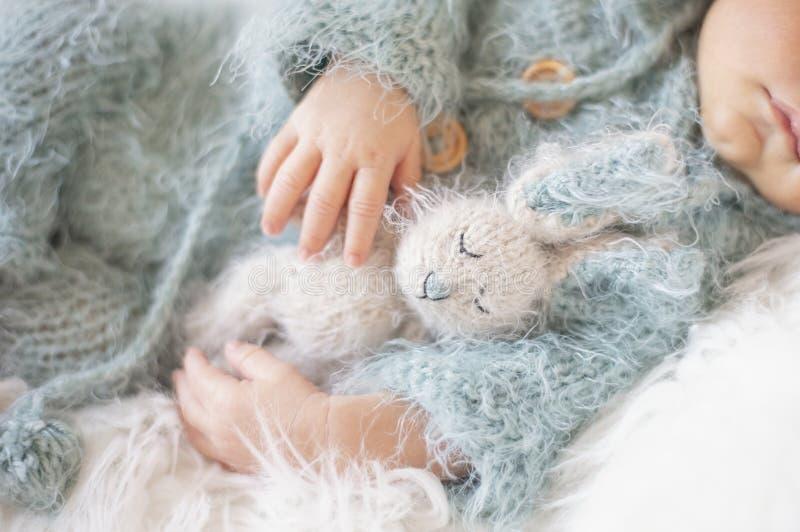 Pasgeboren baby Slaapende baby in bed, terwijl hij een Bunny Toy vasthoudt Baby met blauw-gebreide Romper royalty-vrije stock afbeeldingen