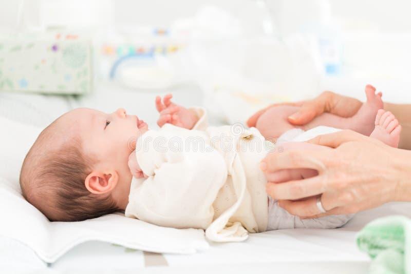 Pasgeboren babydochter die heupoefening doen stock afbeeldingen