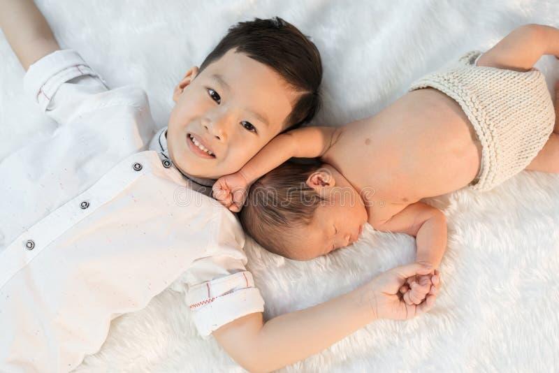 Pasgeboren babyjongen en oudere broer stock afbeelding