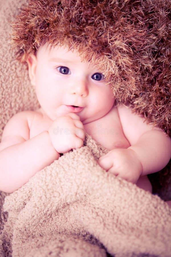 Pasgeboren babyjongen met een pluizige hoed stock fotografie