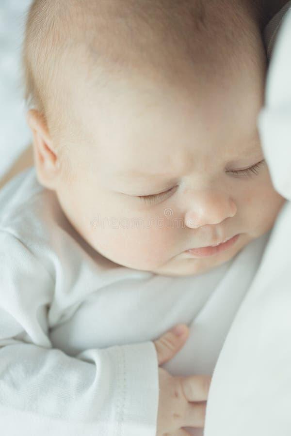 Pasgeboren babyslaap in de wapens van een ouder Portret van zuigeling gekleurd zacht stock foto