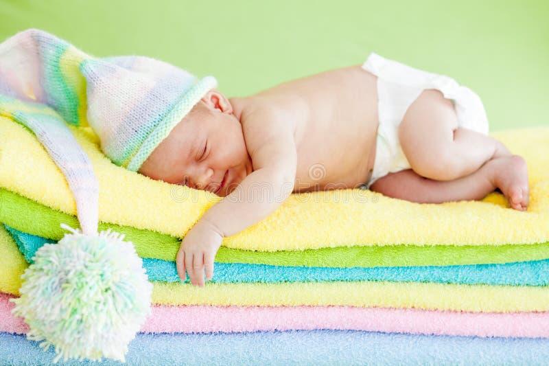 Pasgeboren babyslaap op kleurenhanddoeken stock afbeelding