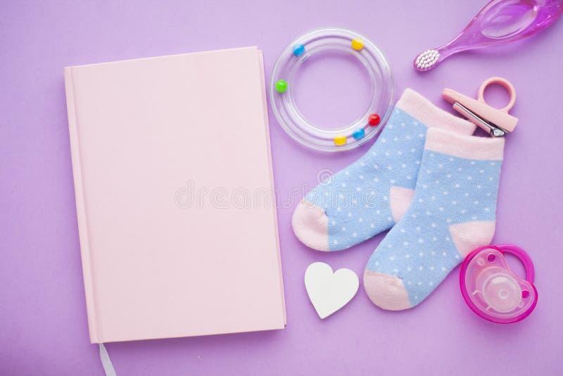 Pasgeboren babyverhaal Strowhart en het speelgoed van kinderen, schaar, zuigfles, uitsteeksel, haarborstel op violette achtergron royalty-vrije stock fotografie