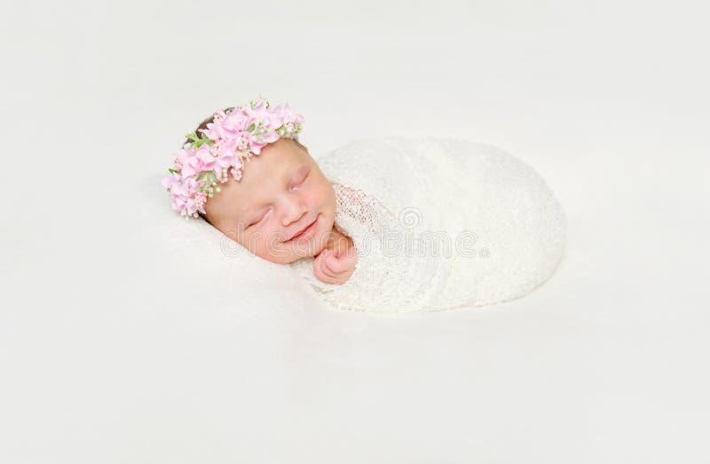 Pasgeboren die baby in het witte luier in slaap glimlachen wordt ingewikkeld royalty-vrije stock afbeeldingen