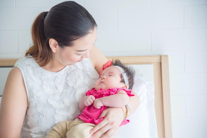 Pasgeboren slaap terwijl moeder die haar houden in slaapkamer stock afbeelding