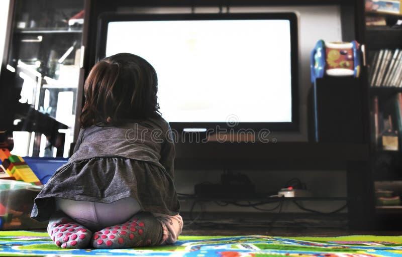 Pasgeboren TV van het babyhorloge op het tapijt in woonkamersokken steunt mening stock afbeelding