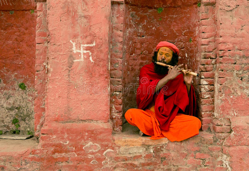 Pashupathinath Mandir, Katmandu, Nepal - Jan 01, 2017 The musician. Man is sitting on the bench and he is playing on fluet. He is lean against the saffron wall royalty free stock photos