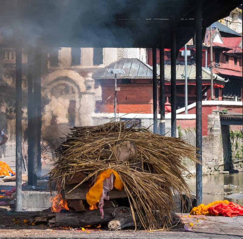 Pashupatinath temple cremations on the Bagmati River. Cremation ceremony at Pashupatinath temple on the Bagmati River stock images