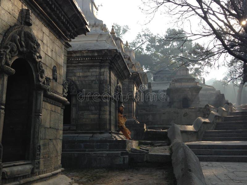 Pashupatinath Temple in Kathmandu. Hindu monk is sitting in the corner of Pashupatinath Temple royalty free stock image