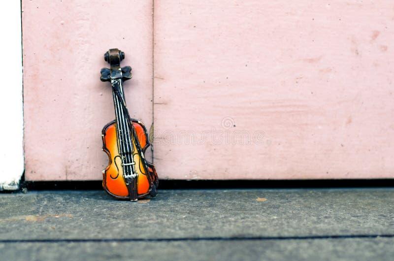 Pasión de la música y concepto de la afición, miniatura del violín sobre la pared de madera con tono retro del color fotografía de archivo libre de regalías