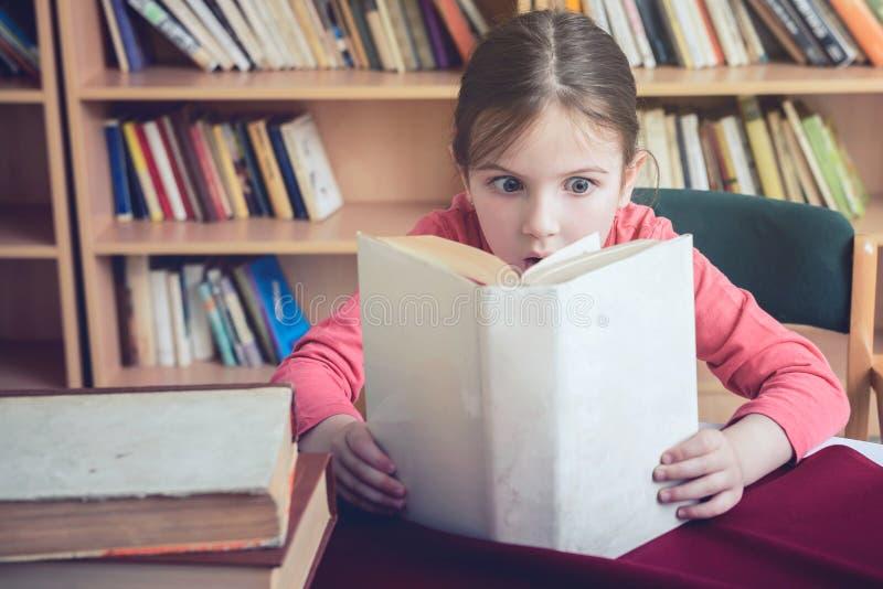 Pasión linda de la niña para leer foto de archivo