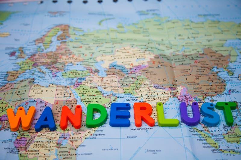 Pasión por los viajes escrita con los bloques del juguete en un mapa del mundo imágenes de archivo libres de regalías