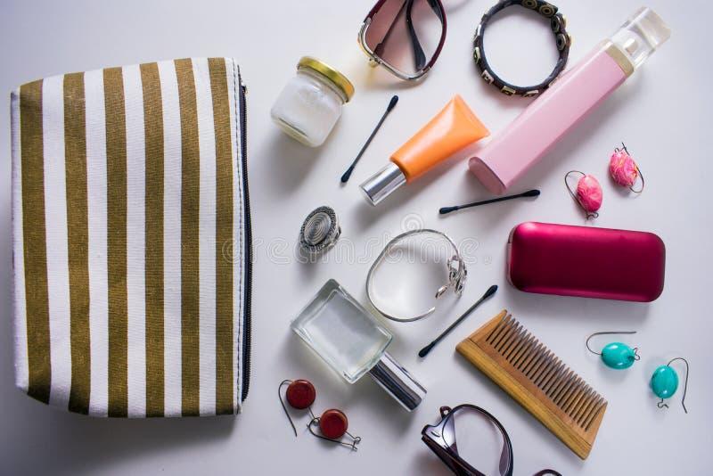Pasiasta kosmetyczna torba z różnorodnymi kosmetycznymi produktami na białym tle obraz royalty free