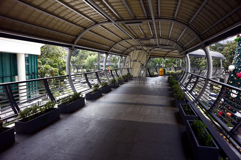 Covered elevated foot bridge at the Ortigas Center in the central business district of Pasig City. Pasig City, Philippines - January 6, 2020 - Covered elevated stock photography