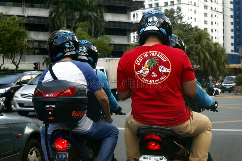 Passengers and drivers of a motorcycle taxi wait at an intersection for the stoplight to turn green. Pasig City, Philippines - January 11, 2020: Passengers and stock images