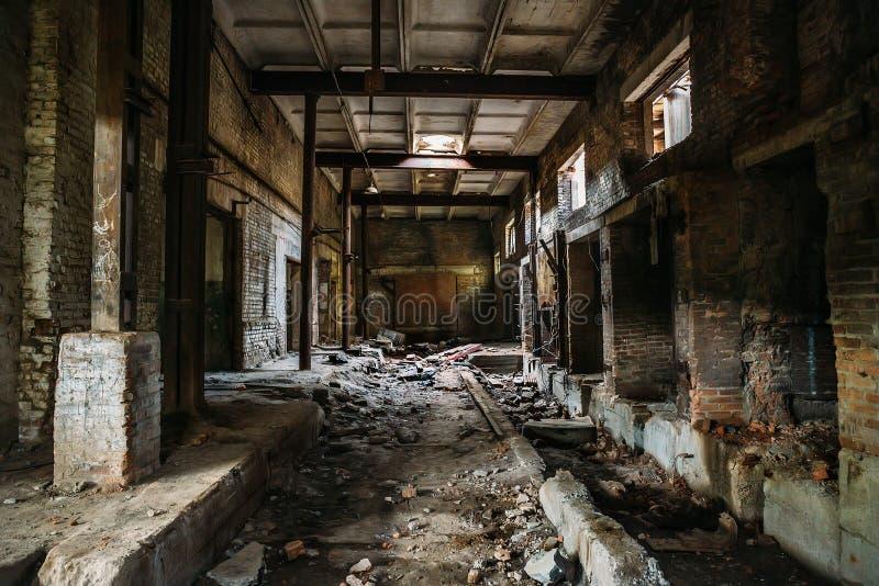 Pasillo asustadizo oscuro en la fábrica arruinada industrial abandonada del ladrillo, interior espeluznante, perspectiva imagen de archivo