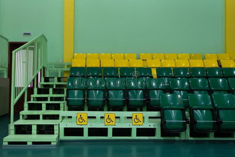 Pasillo de deportes de los asientos que asienta Asientos verdes y amarillos y asientos para los minusválidos Copie el espacio Ter fotografía de archivo