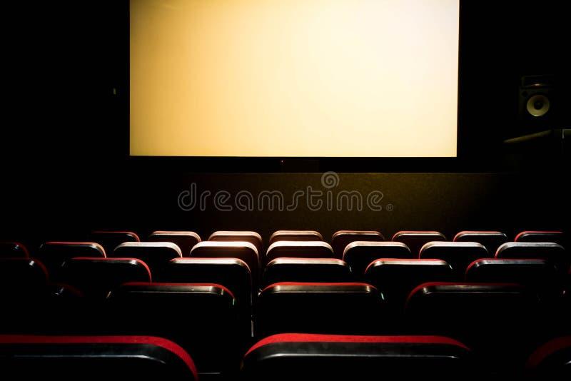 Pasillo del cine de la película con una premier vacía blanca de la pantalla con los asientos rojos fotos de archivo