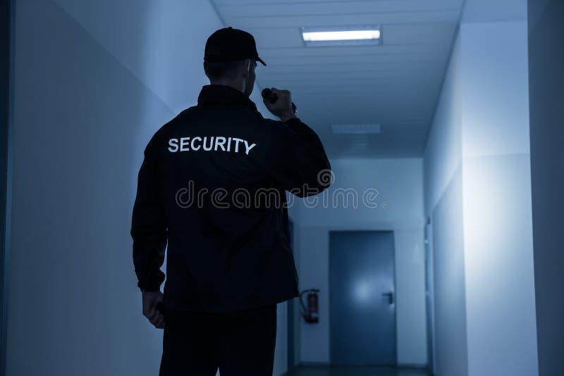 Pasillo del edificio de With Flashlight In del guardia de seguridad foto de archivo